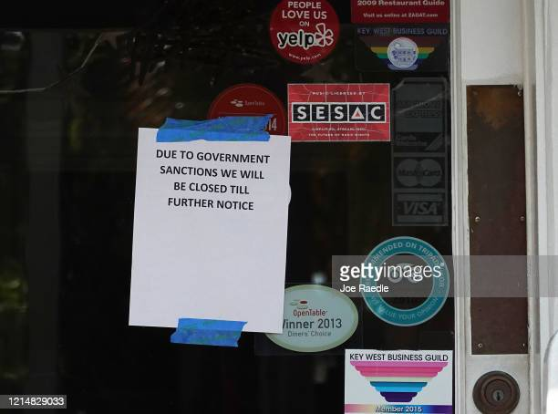 A sign reads 'Due to Government Sanctions we will be closed till further notice' on the door to a business as the city government takes steps to...