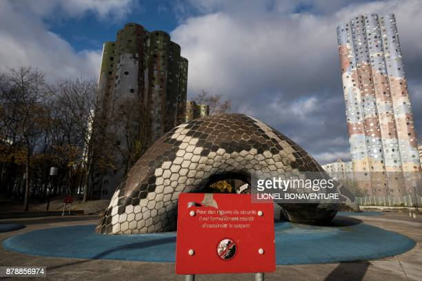 A sign reads 'For security reasons it is strictly forbidden to climb the snake' in front of a large snake shaped sculpture designed by Laurence Rieti...