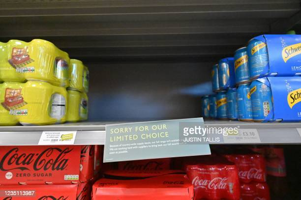 """Sign reads """"Sorry for our limited choice"""" on a display of canned drinks inside a Waitrose supermarket in London on September 7, 2021. - Sparse..."""