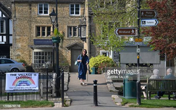 A sign reads This Village is Closed as a woman walks past elderly people sat on a bench in the Cotswolds village of BourtonontheWater central...