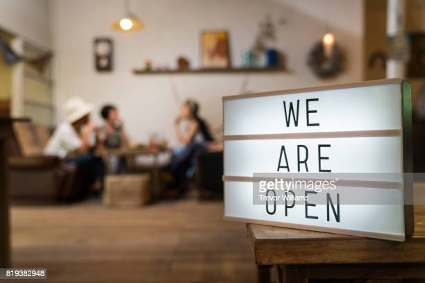 A sign reads 'we are open' in front of a cafe