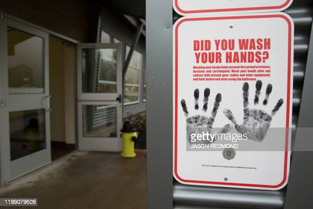 A sign reminding people to wash their hands is pictured outside a dormitory at the Washington State Patrol Fire Training Academy which has been...