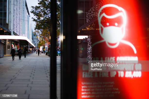 Sign reminding public transport users to wear face coverings lights up the digital advertising screen of a bus stop on a quiet Oxford Street in...