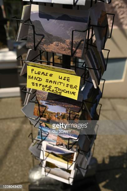 Sign reminds people to use the hand sanitiser while browsing for postcards in Keswick in the Lake District in north west England on August 14 as many...