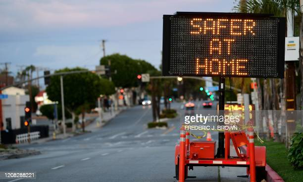 A sign reminds residents it is 'Safer at Home' on the quiet streets of Monterey Park California on March 26 2020 as desert the streets due to the...