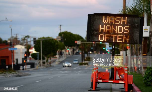 A sign reminds residents to 'Wash Hands Often' on the quiet streets of Monterey Park California on March 26 2020 as people stay at home due to the...
