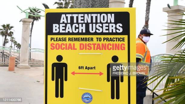 A sign reminds the public of social distancing guidelines at Huntington Beach California on April 30 2020 California Governor Gavin Newsom announced...