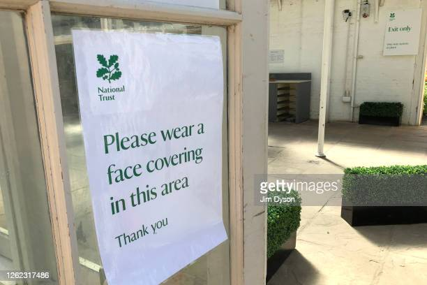 A sign requesting patrons wear face masks is displayed on the door of a cafe at Cliveden House on July 28 2020 in Taplow United Kingdom Many UK...