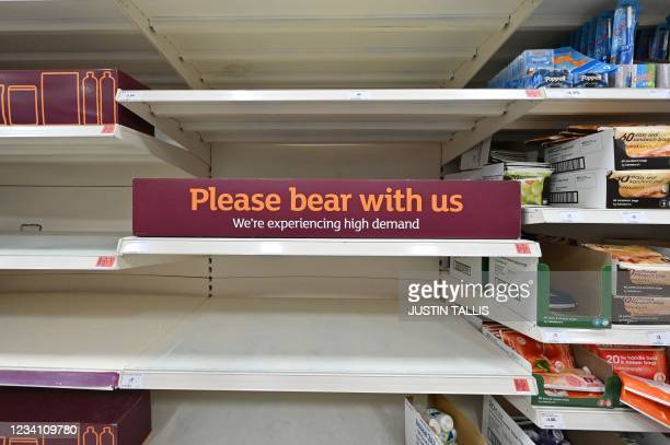 Sign requesting shoppers' patience about products temporarily out of stock is displayed on empty shelves in a supermarket at Nine Elms, south London...