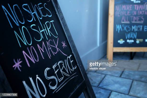 Sign requiring a face mask at SpeakEasy Bar & Grill on May 09, 2020 in Newport, Rhode Island. Non-critical retail establishments began opening their...