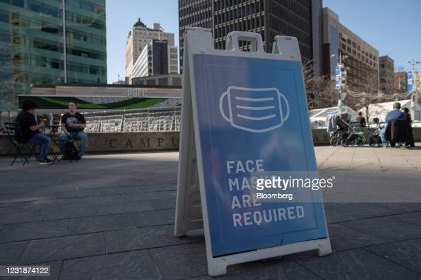 Sign requiring protective face masks in Campus Martius in Detroit, Michigan, U.S., on Sunday, March 21, 2021. After seeing declines in Covid-19 case...