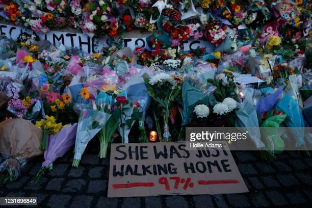"""Sign saying """"SHE WAS JUST WALKING HOME 97%"""" is seen among the flowers and candles on Clapham Common where floral tributes have been placed for Sarah..."""