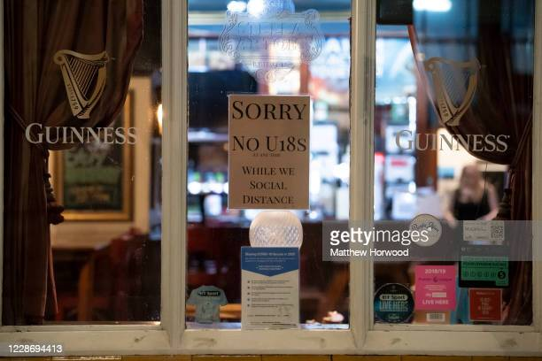 Sign saying Sorry no under 18s in a pub window on September 24, 2020 in Cardiff, Wales. Pubs, cafes and restaurants in Wales will have to shut at...