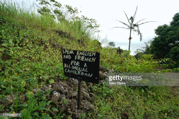A sign saying Speak English or French for a bilingual Cameroon outside a now abandoned school on May 22 2019 in a rural part of SW CameroonIn 2017...