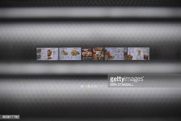A sign seen through the shutters on a closed KFC fast food store in south London is closed on February 19 2018 shows the menu US fast food chain KFC...