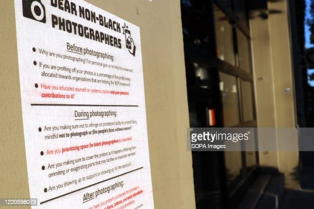 """Sign setting out rules for non-Black photographers is seen on the side of a building inside Seattle's so-called """"Capitol Hill Autonomous Zone.""""..."""