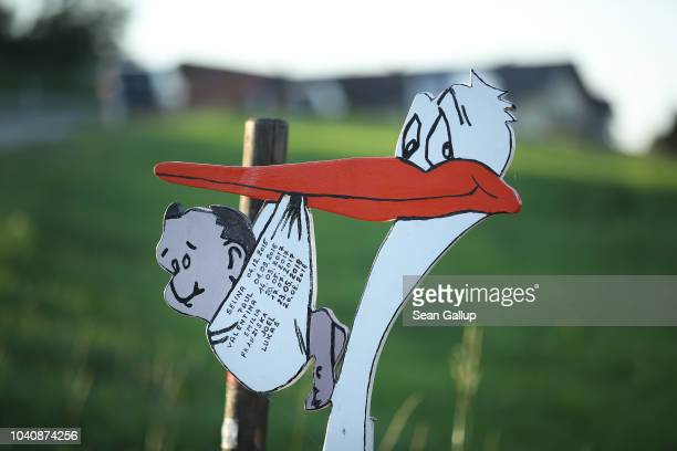 A sign showing a stork carrying a newborn baby advertises the services of a midwife on September 21 2018 near Laufen Germany Midwives in Germany...
