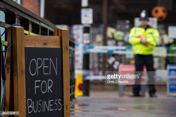 A sign showing local businesses are open next to police officers at a cordon near the scene where former doubleagent Sergei Skripal and his daughter...