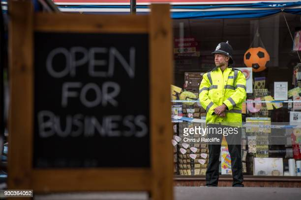 A sign showing that local shops are open for business stands near a police officer at a cordon near to the bench where investigations continue into...