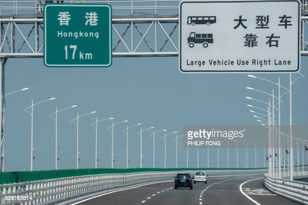 A sign shows the distance to Hong Kong as vehicles travel along a section of the Hong KongZhuhaiMacau Bridge in Zhuhai on March 28 2018 Officials say...