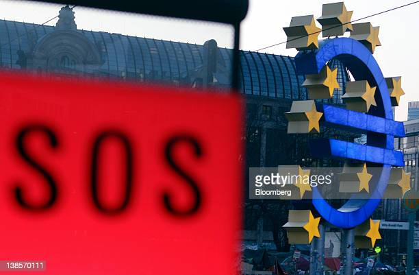 A SOS sign sits an emergency phone box in front of a Euro sign sculpture near the European Central Bank's headquarters in Frankfurt Germany on...