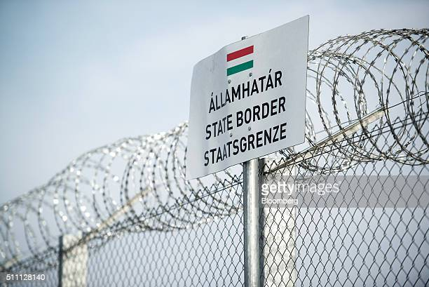 A sign sits beside a razor wired topped security fence on the HungarianSerbian border near Roszke Hungary on Wednesday Feb 17 2016 The European Union...