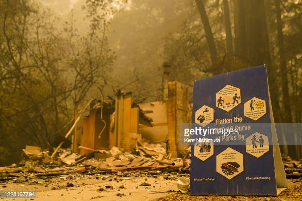 Sign sits in front of a burned structure as Smoke hangs low in the air at Big Basin Redwoods State Park as some redwoods are still on fire on...