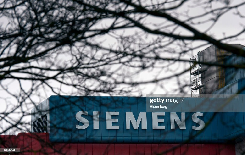 A sign sits on a Siemens AG building in Munich, Germany, on Monday, Jan. 23, 2012. Siemens AG has earmarked more than 1 billion euros ($1.3 billion) to expand production of gas-turbines and fend off General Electric Co. as they jostle for share of the expanding market. Photographer: Guenter Schiffmann/Bloomberg via Getty Images