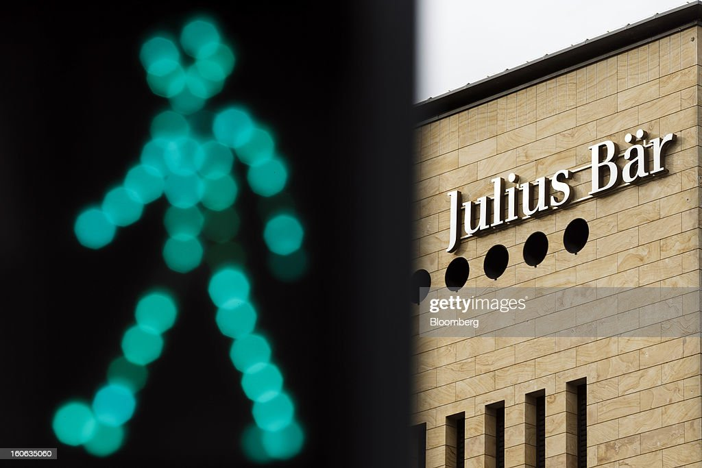A sign sits on a wall outside the offices of Julius Baer Group Ltd., near an illuminated pedestrian crossing lamp, in Geneva, Switzerland, on Sunday, Feb. 3, 2013. Julius Baer Group Ltd., the third-largest Swiss wealth manager, reported declining revenue margins on assets under management as full-year profit matched analyst estimates. Photographer: Valentin Flauraud/Bloomberg via Getty Images
