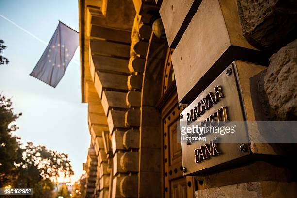 Sign sits on display at the entrance to the Hungarian central bank, also known as Magyar Nemzeti Bank, as a flag of the European union flies in the...