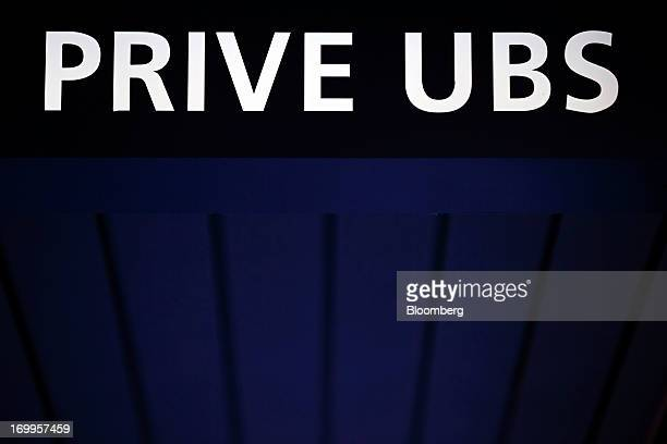 A sign sits on the roof of a UBS AG bank branch in Geneva Switzerland on Wednesday June 5 2013 Members of the Swiss parliament's upper house's...