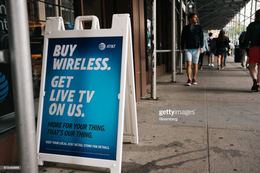 A sign sits outside an AT&T Inc. store location in New York, U.S., on Wednesday, June 13, 2018. AT&T Inc.'s sweeping court victory allowing its takeover of Time Warner Inc. delivers a sharp setback to the Justice Department's new approach to policing mergers under President Donald Trump and promises to spark a merger wave across industries. Photographer: Christopher Lee/Bloomberg via Getty Images