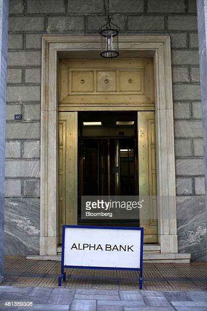 A sign sits outside the open door to an Alpha Bank AE bank branch in Athens Greece on Monday July 20 2015 German Chancellor Angela Merkel held out...