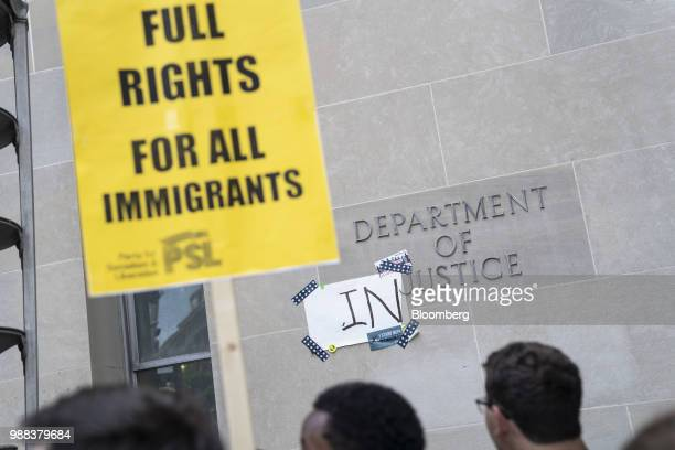 A sign sits taped to the Robert F Kennedy Department of Justice building as demonstrators gather during a protest against the Trump administration's...