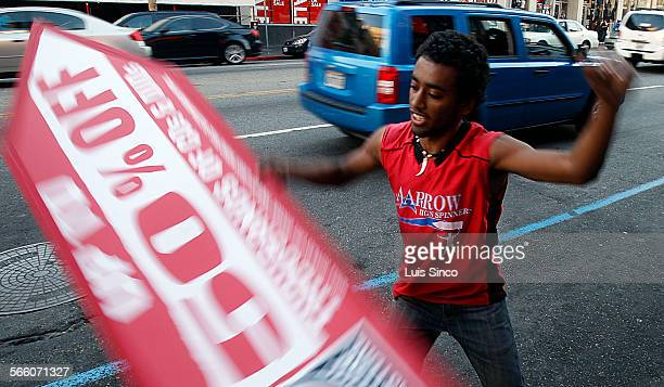 Sign spinner Larry Fuller tries to catch the eyes of passing motorists along Hollywood Blvd on Tuesday Dec 30 as part of a contest by Aarow...