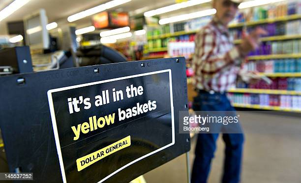 A sign stands near a stack of shopping baskets at a Dollar General Corp store in Creve Coeur Illinois US on Thursday May 31 2012 US consumer spending...