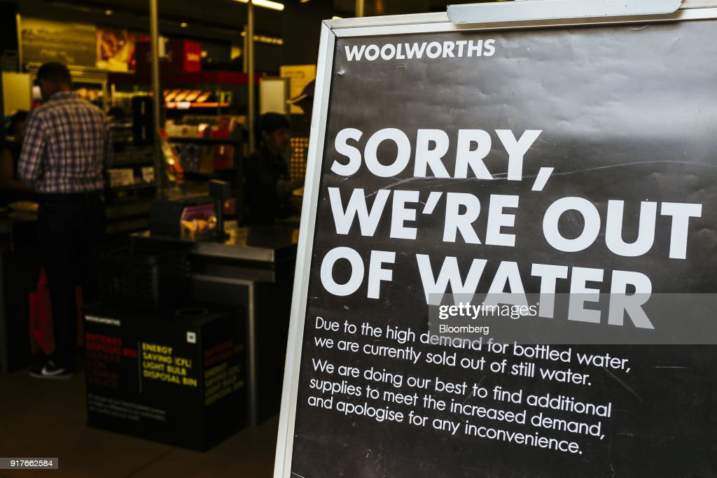 A sign stands outside a store advising customers of no water for sale and reads 'Sorry, We're Out Of water' at a Woolworths Holdings Ltd. store in Cape Town, South Africa, on Thursday, Feb. 8, 2018. Confronted by the worst drought on record after years of disastrously low rainfall, city authorities say they may have to turn off the water entirely on May 11, the famous 'Day Zero,' if reservoir levels keep falling and consumption doesn't slow enough. Photographer: Waldo Swiegers/Bloomberg via Getty Images