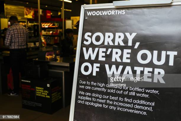 A sign stands outside a store advising customers of no water for sale and reads 'Sorry We're Out Of water' at a Woolworths Holdings Ltd store in Cape...