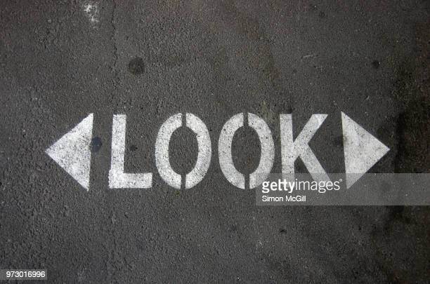 sign stencilled on a road to remind pedestrians to look in both directions before crossing - road marking stock pictures, royalty-free photos & images