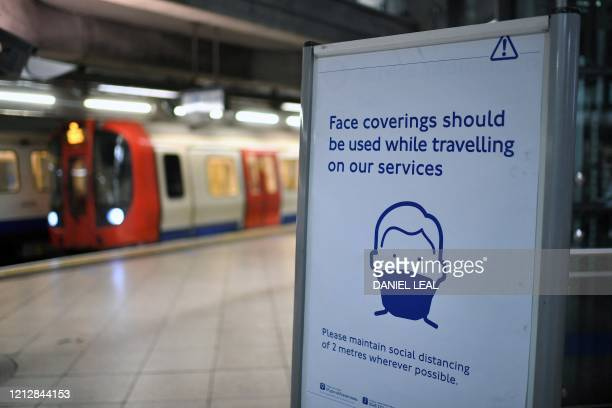 A sign tells commuters that they need to wear PPE of a face covering or mask and observe social distancing as a precautionary measure against COVID19...