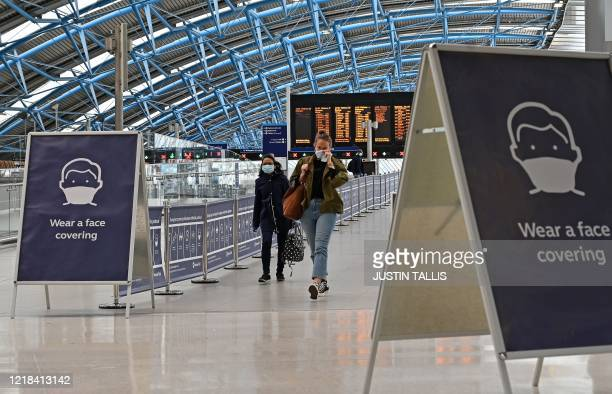 Sign tells passengers to 'wear a face covering' at Waterloo train station in central London , on June 8 as the UK government's planned 14-day...