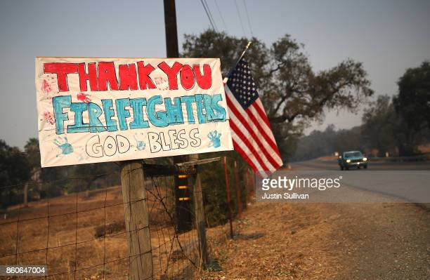 Sign thanking firefighters is posted on Highway 12 on October 12, 2017 in Sonoma, California. Twenty four people have died in wildfires that have...
