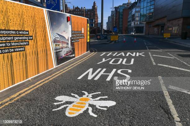 A sign thanking the NHS and a picture of a bee are seen painted on the road close to the Nightingale Hospital North West the converted Manchester...
