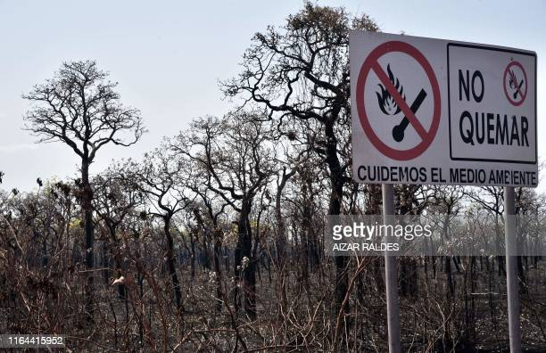 """Sign that reads in Spanish """"Let's take care of the environment"""" is seen at an area afected by forest fires in Otuquis National Park, in the Pantanal..."""