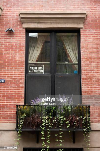 A sign that reads Trump lies all the time is placed at a residential window in Kips Bay as the city continues Phase 4 of reopening following...