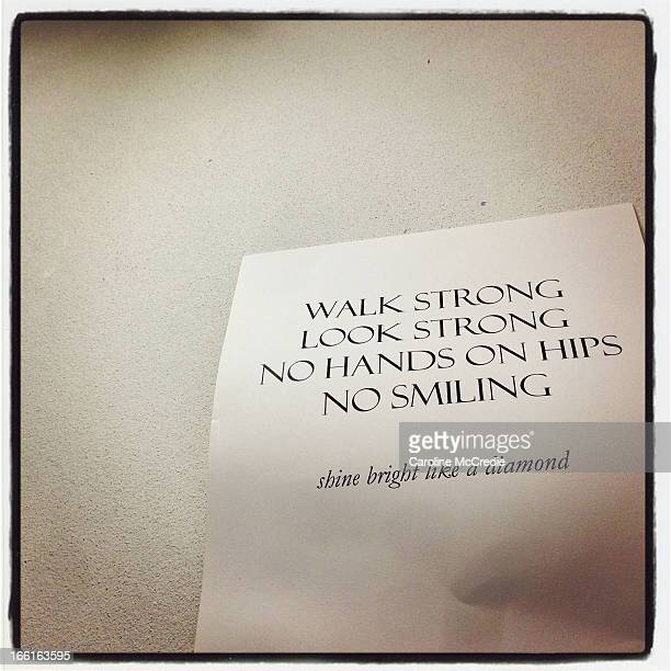 A sign that reads 'Walk Strong Look Strong No Hands On Hips No Smiling' is on display backstage ahead of the Ellery show during the MercedesBenz...