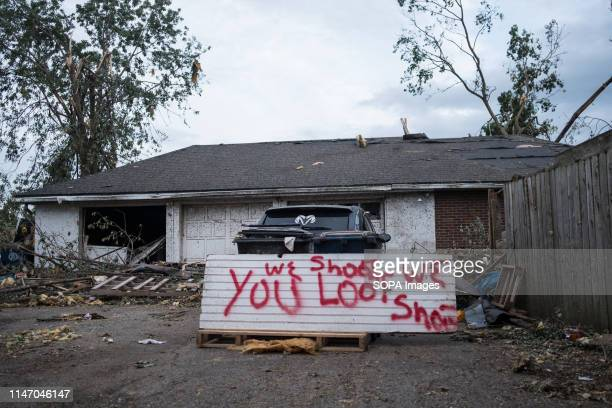 A sign that says you loot we shoot stands outside of a house that was heavily affected by a tornado that hit the area A total of 13 tornados touched...