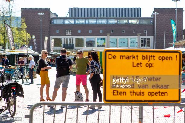 Sign to keep in mind social distancing regulations is seen at a food market amid the coronavirus outbreak on April 11, 2020 in Arnhem, Netherlands....