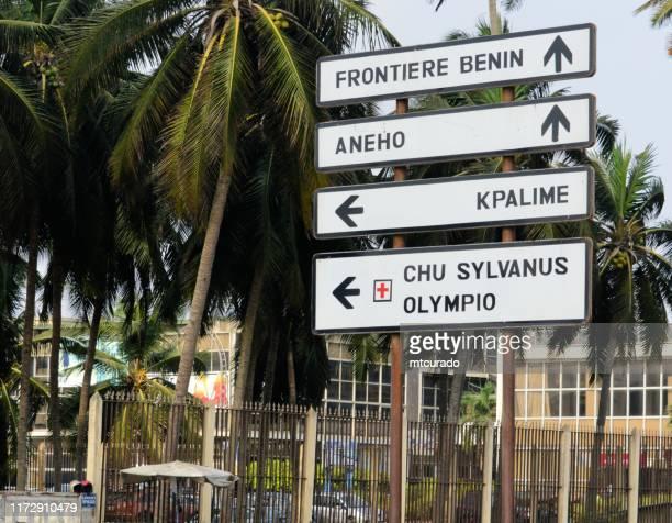sign towards the benin border - boulevard de la république, lomé, togo - togo stock pictures, royalty-free photos & images