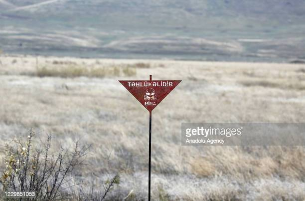 """Sign translates """"Danger"""" on a road between Tartar and Suqovusan as demining works are underway after the area was liberated by Azerbaijani army near..."""
